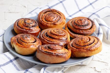 baked cinnamon buns on grey plate on light background with checkered napkin. Top view