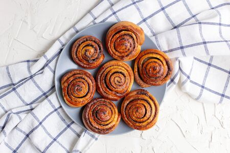 baked cinnamon buns on grey plate on light background with checkered napkin. Top view Stock Photo