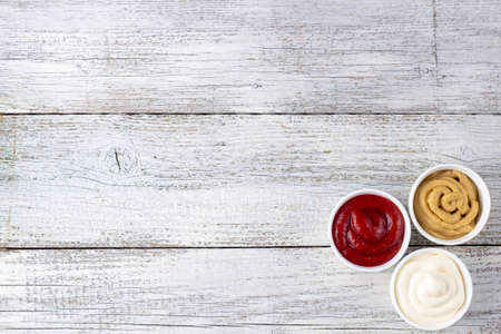 Set of three kinds of classic sauces on white wooden background. Mayonnaise ketchup mustard. top view with copy space Imagens