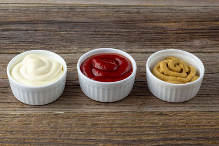 Set of three kinds of classic sauces on natural wooden background. Mayonnaise ketchup mustard