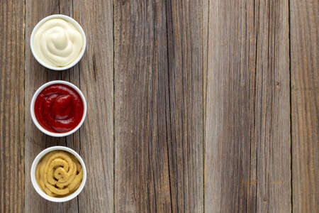 Set of three kinds of classic sauces on natural wooden background. Mayonnaise ketchup mustard. top view with copy space