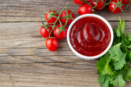 White bowl of tomato sauce with parsley and tomato. Ketchup on natural wooden background. Copy space and top view Imagens