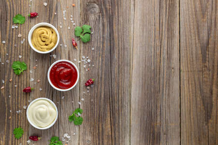 Set of various sauces with spices on natural wooden background. Mayonnaise ketchup mustard. top view with copy space