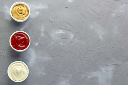 Set of three kinds of classic sauces on gray stone background. Mayonnaise ketchup mustard. top view with copy space