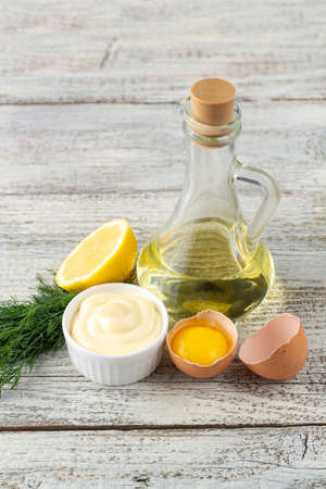 Mayonnaise sauce with lemon, egg, oil and herbs on white wooden background