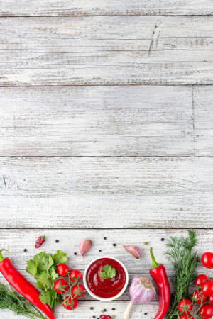 Border of ingredients of tomato sauce. Products for preparing ketchup on white wooden background. Top view with copy space