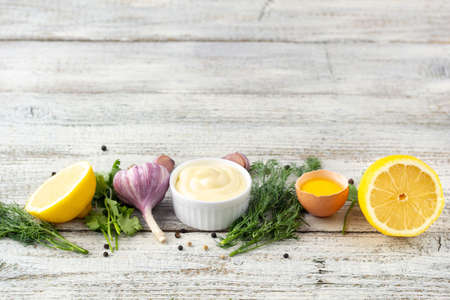 Border of ingredients of garlic sauce. Products for preparing mayonnaise on white wooden background. Top view with copy space