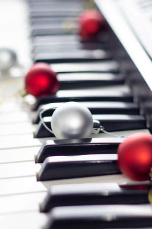 Close up of black and white piano keyboard with christmas ball. New year background with soft focus