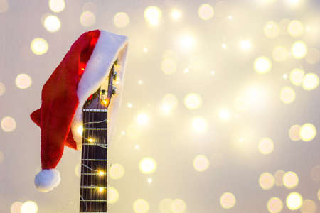 Acoustic Guitar with red Santa hat and light garland with bokeh. Christmas music song concept with copyspace on white background Stock Photo