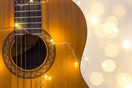 acoustic guitar wrapped in a luminous garland with bokeh. Christmas gift with space for text