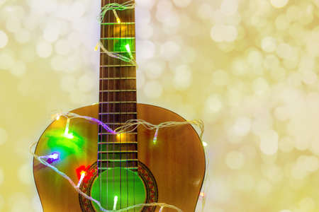 Acoustic guitar wrapped by colorful garland with bokeh. christmas and new year music gift as background