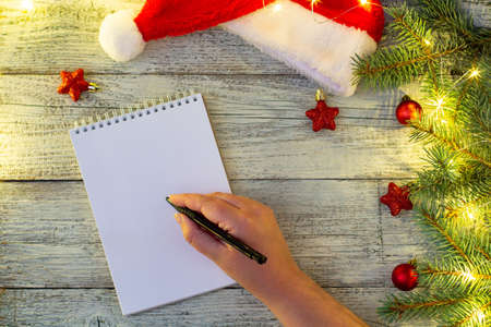 hand of woman writing letter on notepad paper with Christmas decorations and bokeh on white wooden background Stock Photo