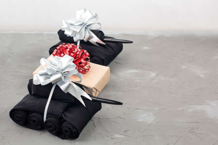 Handmade tanks of socks as gift to men on February 23 on gray background with copy space. And box with red bow Stock Photo