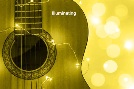 acoustic guitar wrapped in a luminous garland with bokeh. Christmas gift with space for text. Color of the year 2021