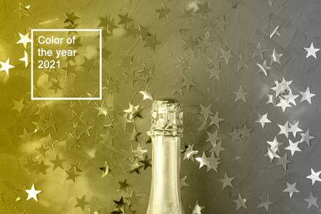 Champagne bottle with gold confetti stars. Concept for christmas, new year, birthday or wedding. Color of the year 2021