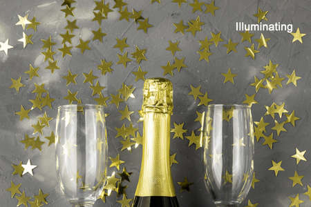 Champagne bottle and glasses with gold confetti stars. Concept for christmas, new year, birthday or wedding