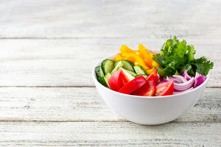 Plate of rainbow salad with different vegetables and herbs in white bowl on white wooden background. With copyspace Stock Photo