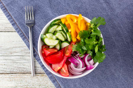 Plate of rainbow salad with different vegetables and herbs in white bowl with blue napkin and fork on white wooden background. Top view Stock Photo