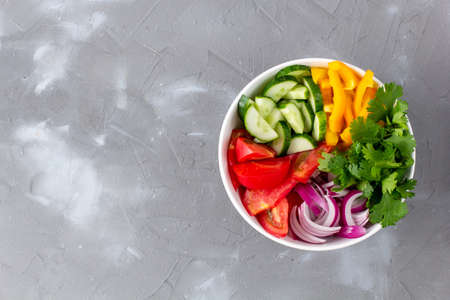 Plate of rainbow salad with different vegetables and herbs in white bowl on gray stone background. Top view with copyspace