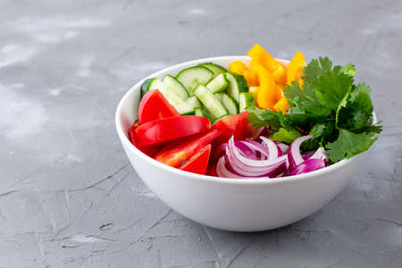 Plate of rainbow salad with different vegetables and herbs in white bowl on gray stone background. With copyspace Stock Photo