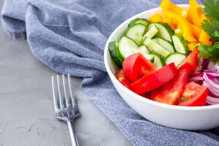Plate of rainbow salad with different vegetables and herbs in white bowl with fork and napkin on gray stone background. Top view with copyspace