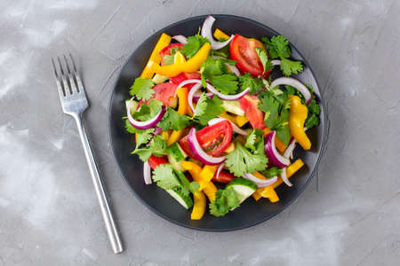 Plate of rainbow salad with different vegetables and herbs on black plate with fork on gray stone background. Top view Stock Photo