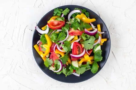 Plate of rainbow salad with different vegetables and herbs on black plate on white stone background. Top view Stock Photo