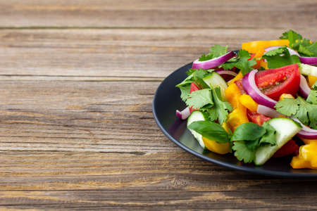 Plate of rainbow salad with different vegetables and herbs on black plate on natural wooden background. With copyspace