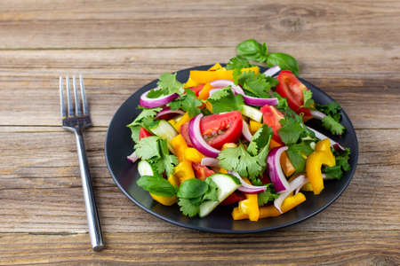 Plate of rainbow salad with different vegetables and herbs on black plate with fork on natural wooden background Stock Photo