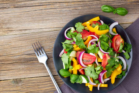 Plate of rainbow salad with different vegetables and herbs on black plate with fork and napkin on natural wooden background. Top view with copyspace Stock Photo