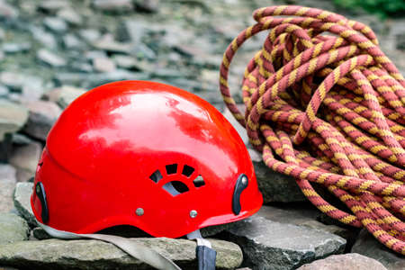 Rope access tools: hard hat, rope, carabiner. Mountaineering equipment on rocks against a background of rocks and greenery