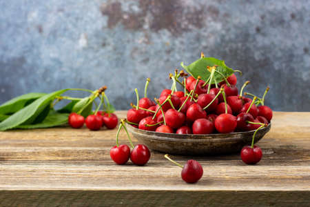 Ripe wet sweet cherries with green leaves in a metal plate on wooden background