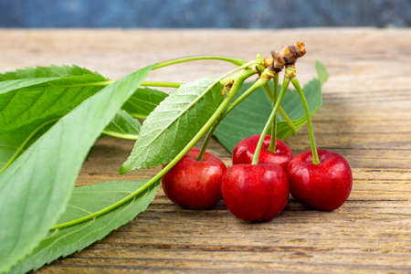 bunch of ripe sweet cherries with green leaves on wooden background Stock Photo