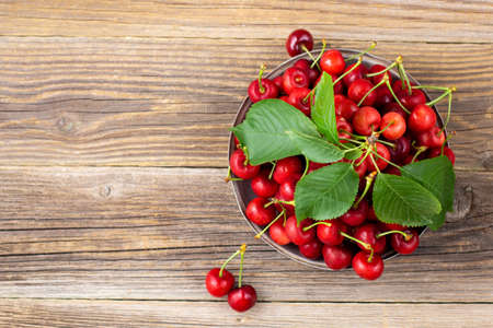 Ripe wet sweet cherries with green leaves in a metal plate on wooden background. Top view with copyspace