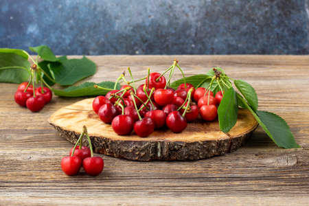 bunch of ripe sweet cherries with green leaves on wooden board