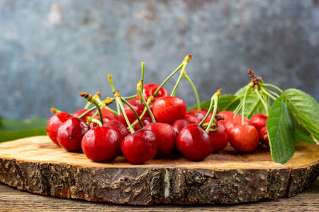 bunch of ripe sweet cherries with green leaves on wooden board. With copyspace Stock Photo