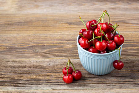 Ripe wet sweet cherries with drops in a blue bowl on wooden background with copyspace