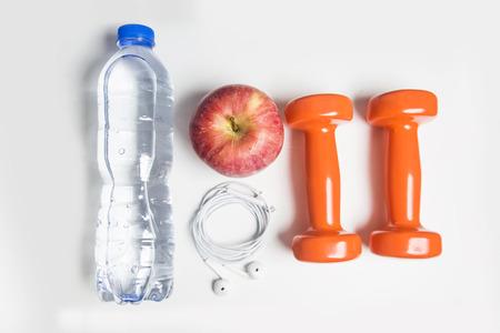sport, gezonde leefstijl en objecten concept - close-up van dumbbells, fitness tracker, oordopjes en een fles water op witte achtergrond