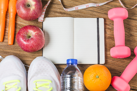 Fitness, healthy and active lifestyles Concept, Bottle of water, dumbbells, sport shoes, smartphone with headphone and apples on wood background. copy space for text. Top view Stock Photo