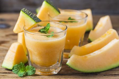 El jugo de melón con la menta en un frasco de vidrio en la mesa. melón macarons Foto de archivo - 85562965
