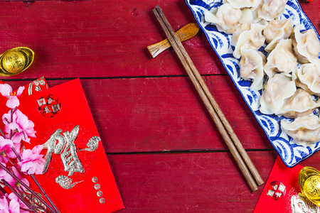 Chinese Jiaozi new year food, spring festival food on traditional spring festival Spring festival atmosphere and dumplings, ang pow or red packet and gold ingots. Chinese characters means luck,wealth Stock Photo