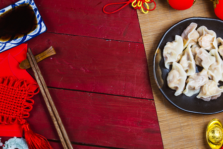 Chinese Jiaozi new year food, spring festival food on traditional spring festival Spring festival atmosphere and dumplings, ang pow or red packet and gold ingots. Chinese characters means luck,wealth Banque d'images