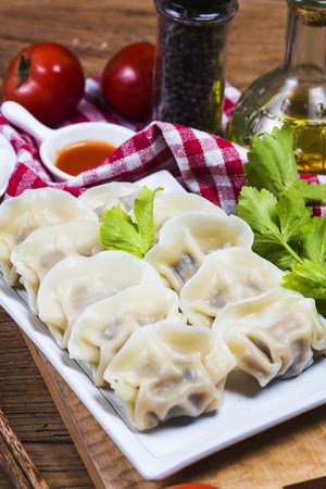 Asian dumplings in bowl, chopsticks, Chinese dumplings for dinner.Chinese dumplings for dinnerlunch. Traditional AsianChinese cuisine.