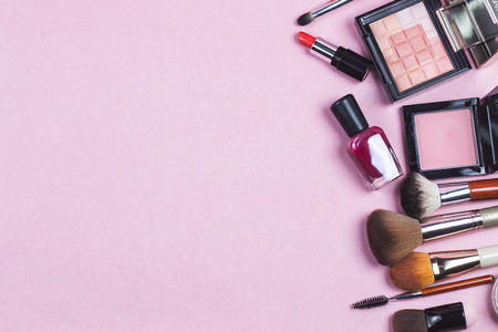 A pink leather make up bag with cosmetic beauty products spilling out on to a pastel background