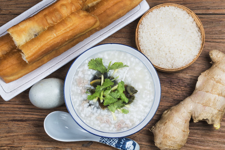 Chinese preserved egg and lean meat porridge with youtiao for breakfast