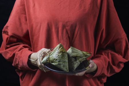 A woman is giving zongzi(rice dumpling) to others as a present on Dragon Boat Festival, Asian traditional food,