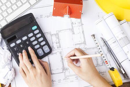 Plan de dibujo a mano en plano con accesorios de arquitecto. El concepto de arquitectura