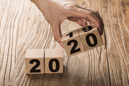 New year 2019 change to 2020 concept hand change wooden cubes. Фото со стока