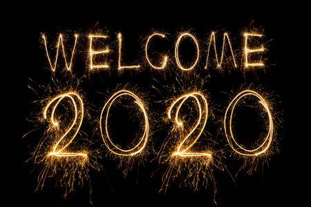 Feliz año nuevo 2020. Texto creativo Feliz año nuevo 2020 escrito brillantes luces de Bengala aisladas sobre fondo negro