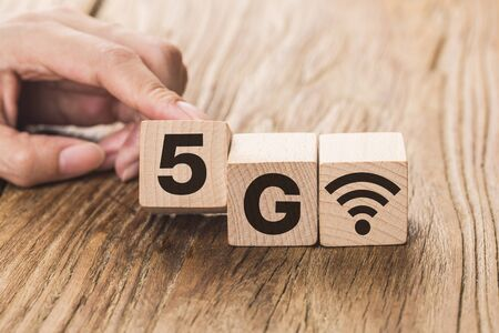 5G (5th Generation) network connecting technology future global. Hand flip wood cube change number 4G to 5G Archivio Fotografico - 131841512